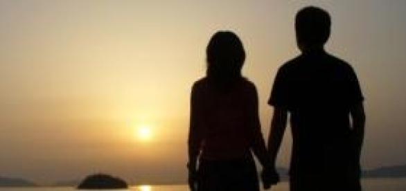 A couple holding hand and watching sunset