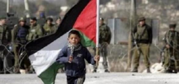 Un enfant courant avec le Drapeau de Palestine