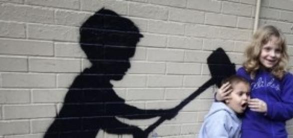 Niños posando con una obra de Banksy.