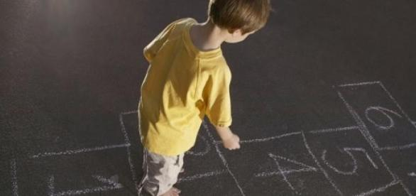 un copil care se joaca sotron