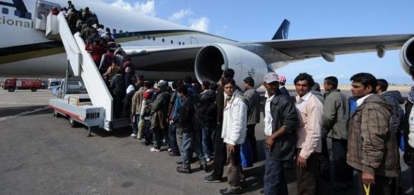 Imigranci zmierzający do samolotem do Europy.