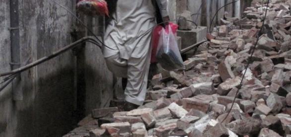 Homem andando em meios aos escombros