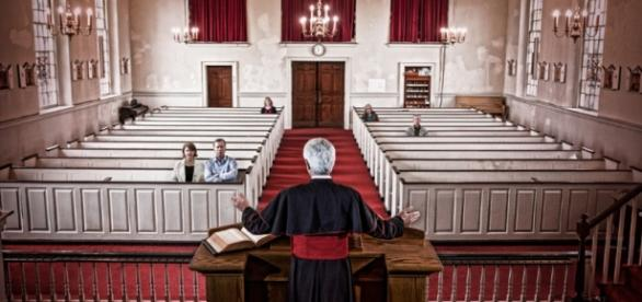 Padre prega numa igreja com poucas pessoas.