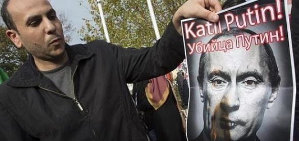 Un hombre quema la imagen de Putin en una protesta