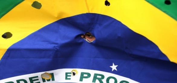"""Bandeira brasileira """"perfurada"""" esteve no protesto"""