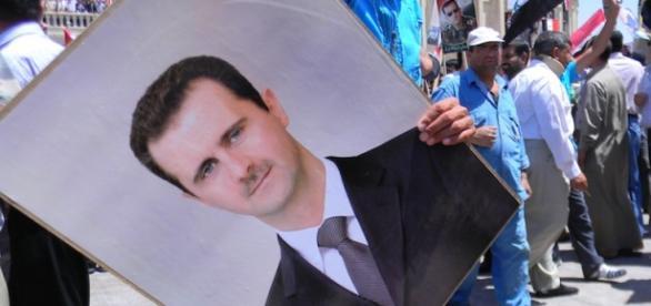 Un manifestante con la foto di Assad