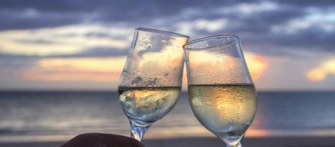 Das Bild wurde auf einem Strand aufgenommen, zwei Gläser mit Sekt sind zu sehen.