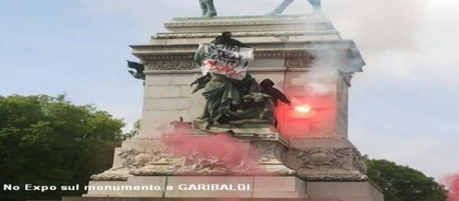 Manifestazione No Global a Milano, manifestanti salgono sul monumento a Garibaldi per esporre il loro cartello