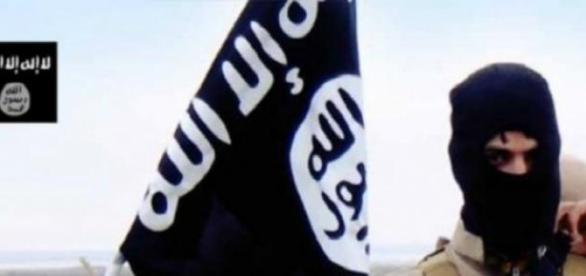 Militante do Estado Islâmico com bandeira do grupo