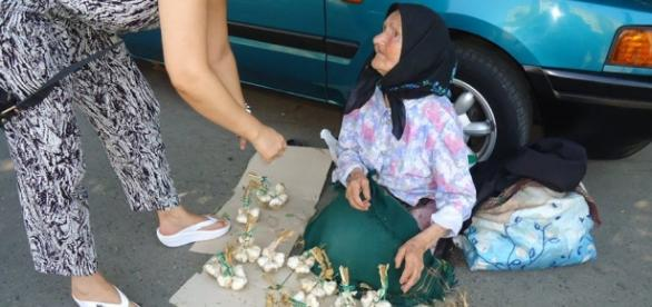 Batrana vinde pe strada cateva legaturi de usturoi