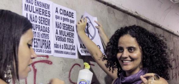 Mulheres colam cartazes contra o Vagão Rosa.