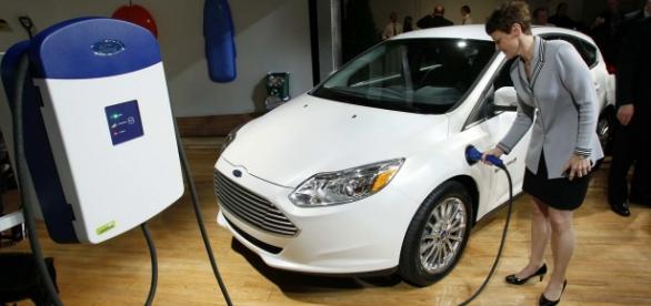 Mujer recargando un coche eléctrico