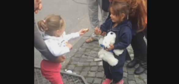 Niña alemana dando caramelos a refugiada siria