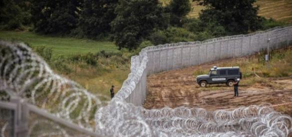 Policiais rondam o muro repelindo imigrantes