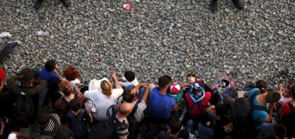 Grupo refugiados tentando embarcar num comboio