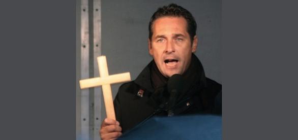 Z krzyżem w ręku nawołuje opamiętania.