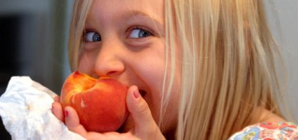 Young kid eating an apricot and smiling.