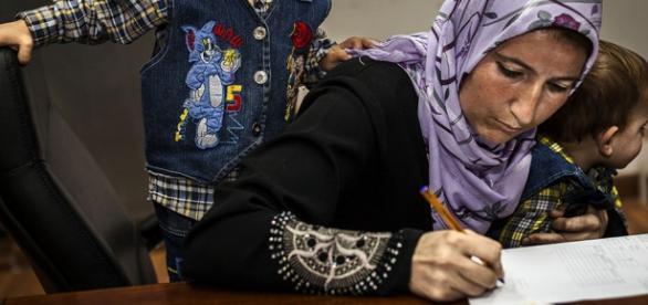 Refugiată completând documentele de înregistrare