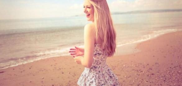 Fotografía de una mujer de la playa sonriendo.