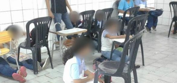 Sem carteiras, alunos assistem aula no chão