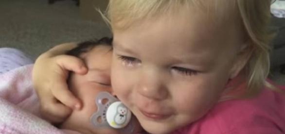 Menina para de chorar ao abraçar a irmã