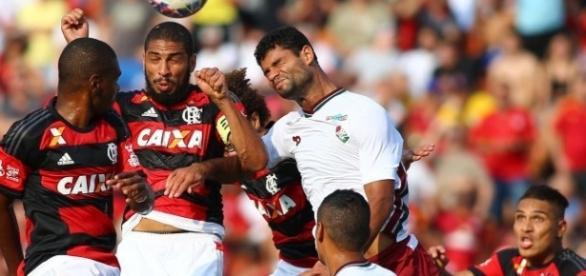 Jogadores de Flamengo e Fluminense, disputam bola aérea.