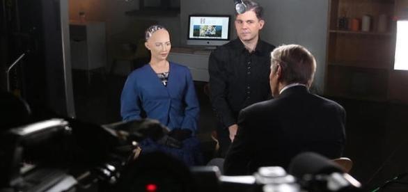 Robô diz que todos os seres conscientes têm alma. À direita, o criador Charlie Rose (CBS NEWS)
