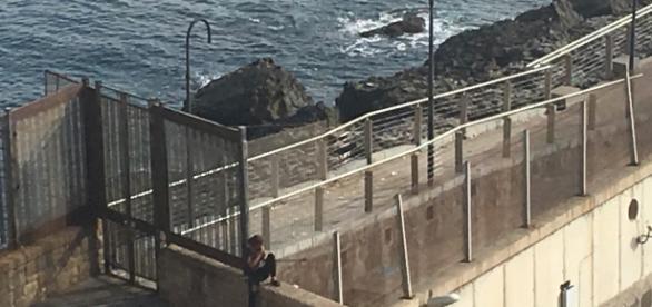 Un niño aguarda junto a las escolleras del puerto de Melilla para colarse.