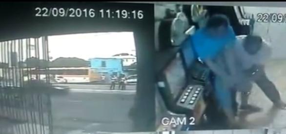 Em uma das cenas gravadas no vídeo é possível ver o policial de camisa azul lutando contra dois homens