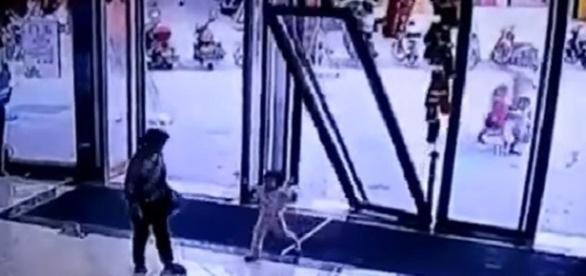 Criança se fere gravemente após porta de vidro cair sobre ela num shopping na China.
