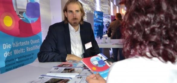 Projektleiter Patrick Durner informiert eine Interessentin über webC@RE. Foto: ©Dagmar Möbius