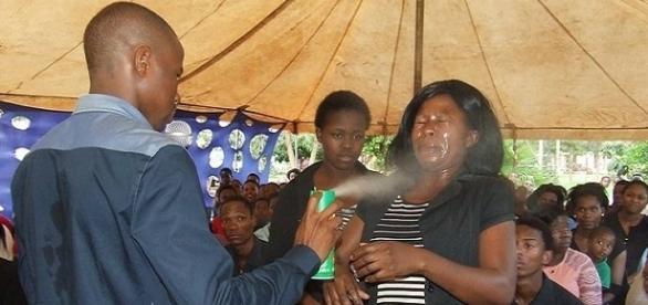 Pastor pulveriza inseticida nos fiéis para curá-los.