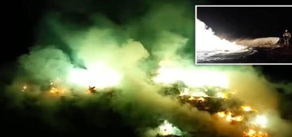 Na imagem, bombeiro, atônito com a ocorrência, combate o fogo (THIRDPHASEOFMOON)
