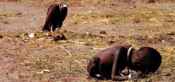 Imagem de criança desnutrida sendo observado por abutre