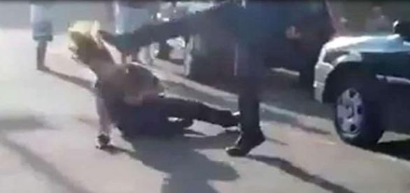 Na imagem a segurança já caída em quanto o homem a atinge com um chute no rosto.