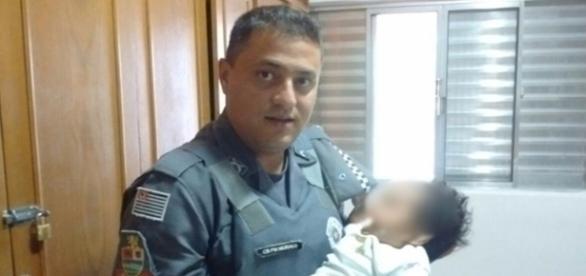 Policial segurando bebê salvo dentro de carro.
