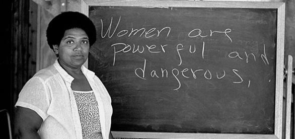 """Audre Lorde junto a una pizarra que dice: """"las mujeres somos poderosas y peligrosas"""""""
