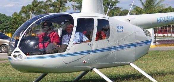 Na imagem o presidente do país, à direita, em um de seus vôos de helicóptero.