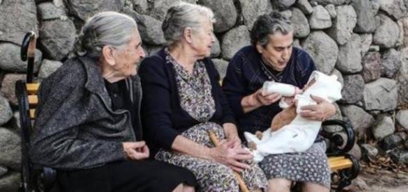A grega Emília, 85, cuida de um neném sírio