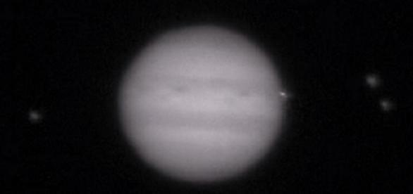 En esta foto pueden observarse las tres lunas de Júpiter y un punto brillante al lado del planeta, procedente del impacto grabado recientemente.