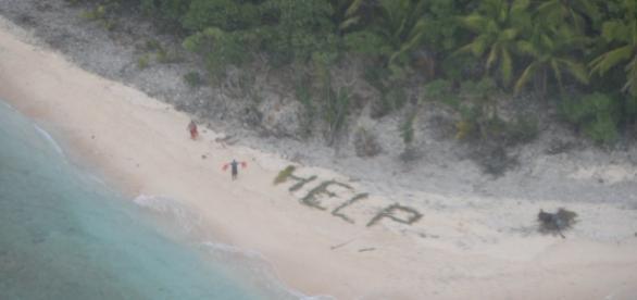 Bărbații salvați de pe insula pustie făcând semne avionului cu vestele de salvare lângă cuvântul HELP - Foto: US NAVY