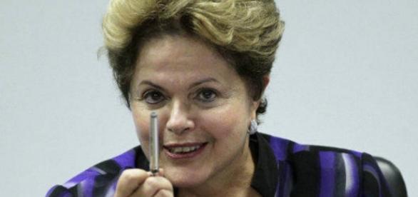 Dilma Rousseff com caneta na mão