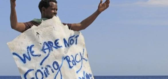 "Imigrant afisând mesajul: ""Noi nu mergem înapoi"""