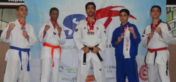 Alunos exibem medalhas ao lado no mestre