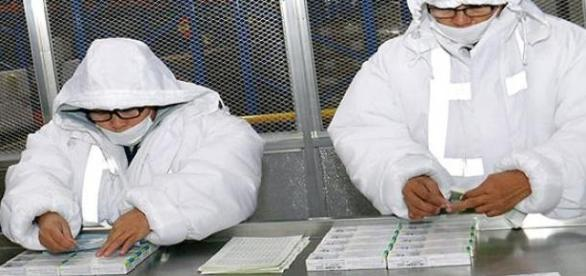 Especialistas do laboratório inspecionando a vacina contra a dengue.