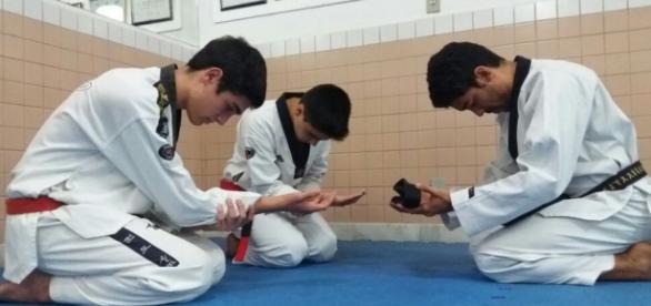 Matheus e Lucas recebem suas faixas das mãos do mestre que carregou a Tocha