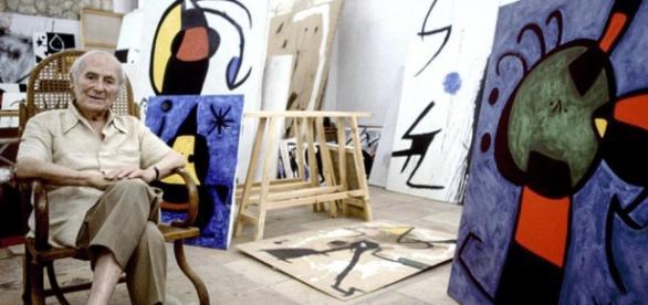 Joan Miró en su estudio con algunos de sus cuadros.