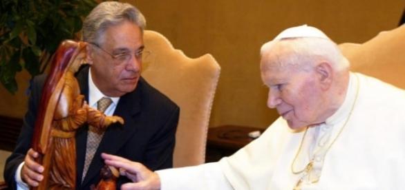 Papa toca a imagem da Santa Paulina durante sua visita ao Brasil em 2002