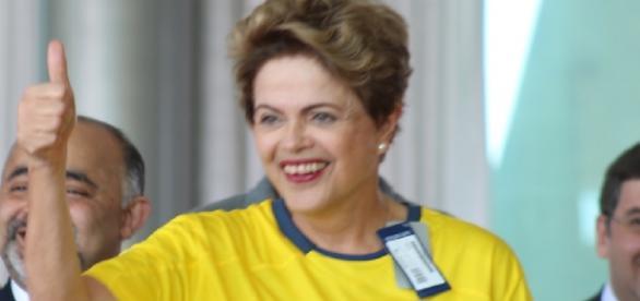 Dilma veste blusa do Brasil e faz sinal de positivo