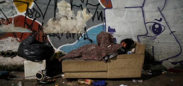 Morador de rua deitado em sofá durante noite fria na capital paulista (Foto: Nacho Doce/Reuters)